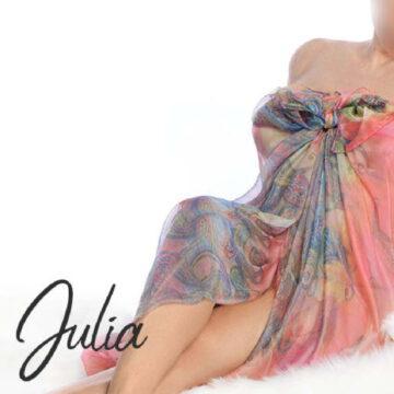 Julia nackt in ein buntes Tuch gehüllt.