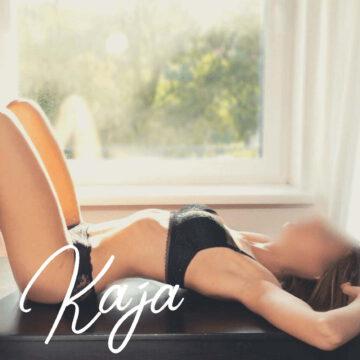 Kaja auf dem Rücken liegend vor einem Fenster in schöner schwarzer Unterwäsche, bereit für eine Tantra Massage.