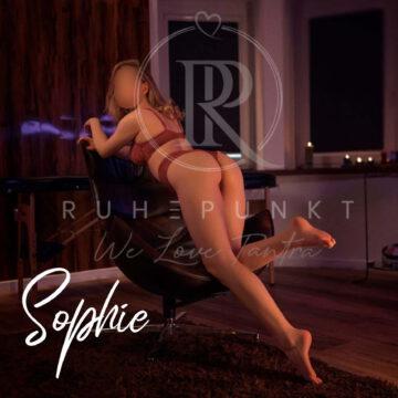 Sophie in süßer roter Reizwäsche streckt ihren Popo Richtung Kamera.
