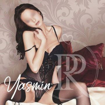 Die unglaublich süße Yasmin mit langen brünetten Haaren sitzt mit gespreizten Beinen auf dem Bettrand und trägt dabei nicht weiter als ein schwarzes Spitzenkorsett, einen durchsichtigen Stringtanga und erotische halterlose Strümpfe.
