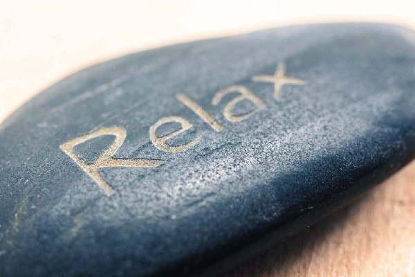 """Ein schöner grauer Stein in einem Massagestudio auf dem """"Relax"""" eingraviert ist."""