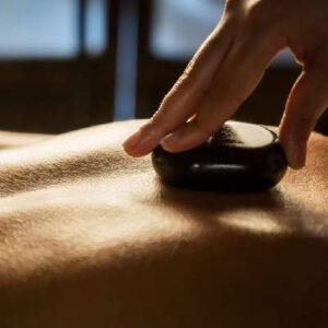 Ein heisser Stein auf dem Rücken eines Patienten. Eine Hot Stone Massage ist eine klassische EWntspannungsmassage.