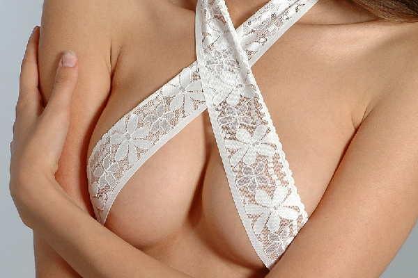 Oberkörper einer nackten Frau, deren wunderschöne Brüste mit weißer Spitze bedeckt sind, freut sich auf eine Yoni Massage.