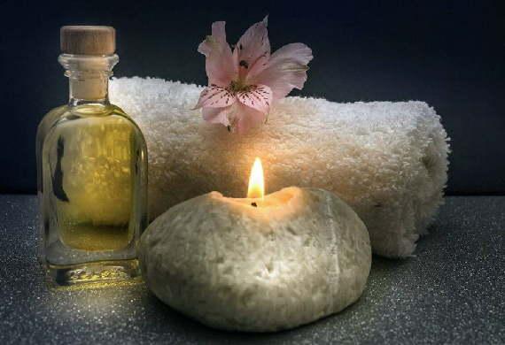 Massageöl, Handtuch und Kerze bei einer Wellness Massage.