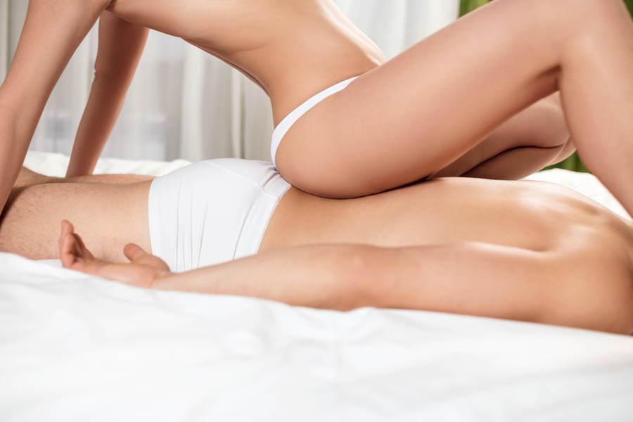 Eine nackte Frau gibt einem Mann eine erotische Massage für Männer auf einem großen Bett.