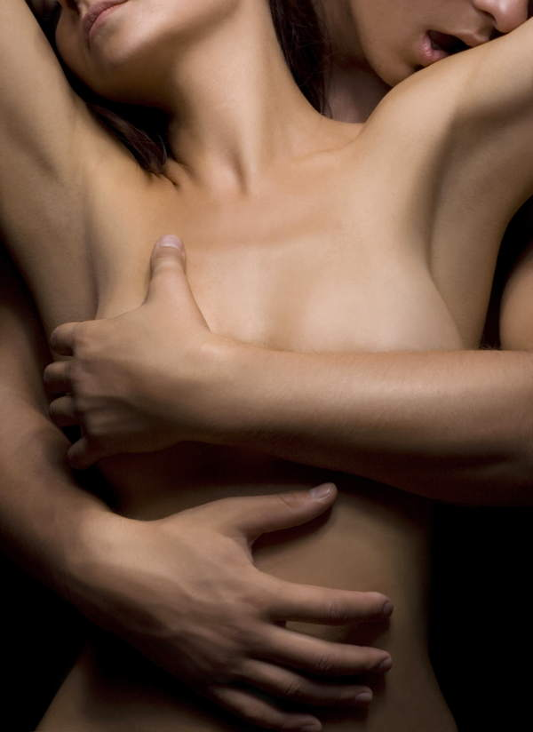 Ein Mann legt bei einer Massage für Paare von hinten seine Hände auf die nackten Brüste einer Frau.