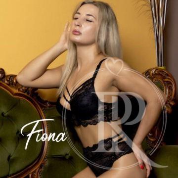 Die sehr hübsche Fiona mit geschlossenen Augen, langen blonden haaren und sexy schwarzer Wäsche.