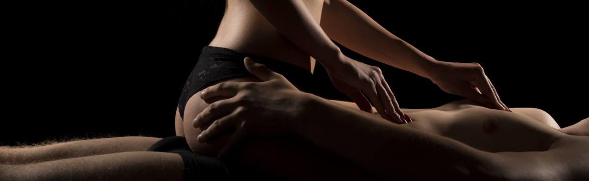 Ein nackter Mann und eine Frau in einem schwarzen Slip geben sich eine Tantra Massage
